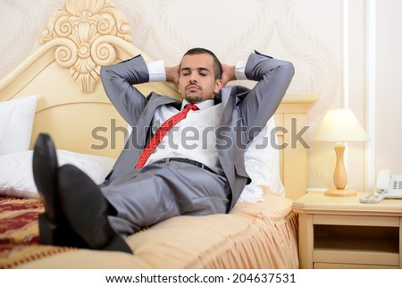 Portrait of Asian businessman with a suitcase, sitting on a bed in a hotel room