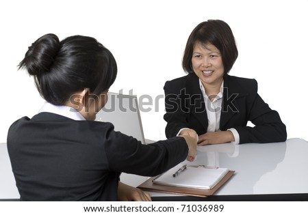 Portrait of Asian businesswoman shaking hands with colleague - stock photo