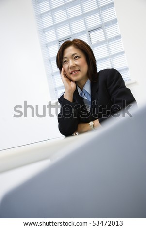 Portrait of Asian businesswoman sitting at desk smiling. - stock photo
