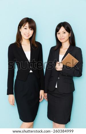 portrait of asian businesswomen on blue background - stock photo