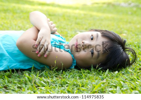 Portrait of Asian child lying on garden grass looking side