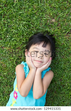 Portrait of Asian child lying on garden grass looking up - stock photo