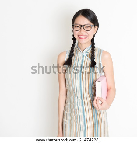 Portrait of Asian Chinese college girl hands holding text books in retro revival style cheongsam standing on plain background. - stock photo