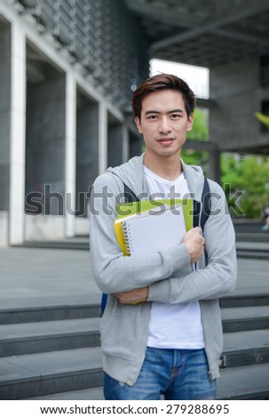 Portrait of asian college student holding book at his university - stock photo