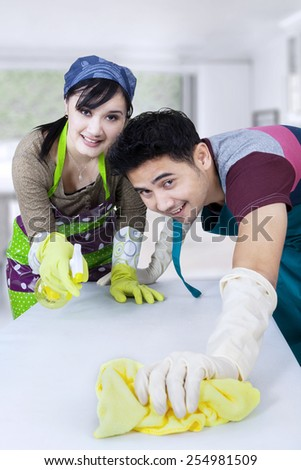 Portrait of asian couple cleaning a table with spring cleaning tools at home - stock photo