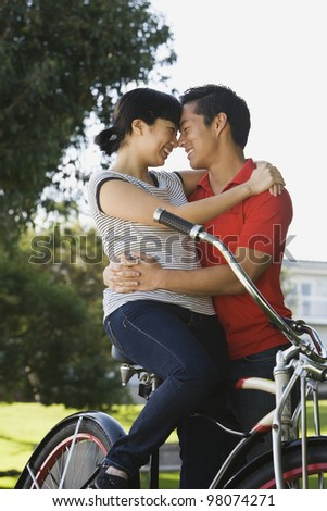 Portrait of Asian couple hugging on bicycle