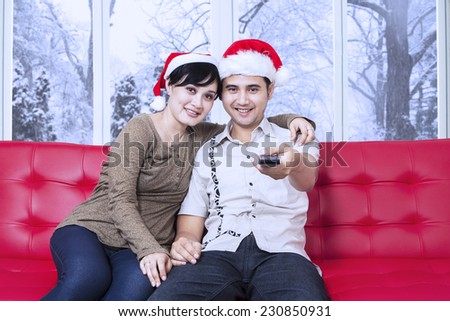 Portrait of asian couple sitting on sofa and wearing christmas hat, watching tv together with winter background on the window - stock photo
