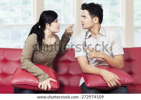 Portrait of asian couple sitting on sofa at home and quarreling - stock photo