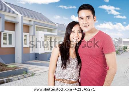 Portrait of Asian couple smiling at the camera and standing near their new home - stock photo