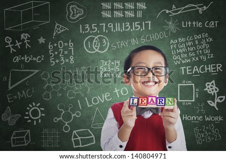 Portrait of asian elementary school student showing LEARN word in class - stock photo