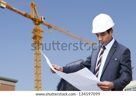 Portrait of asian engineer reading a drawing - stock photo