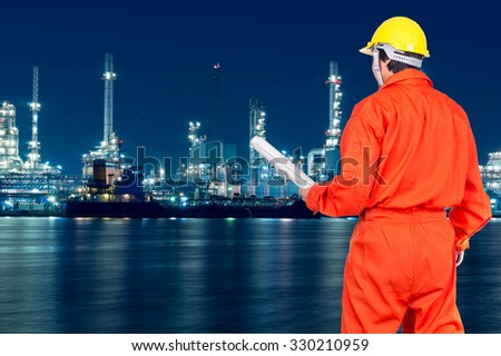 Portrait of Asian engineers holding the blueprint on Oil and gas refinery or Petrochemical factory at twilight time, industrial concept - stock photo