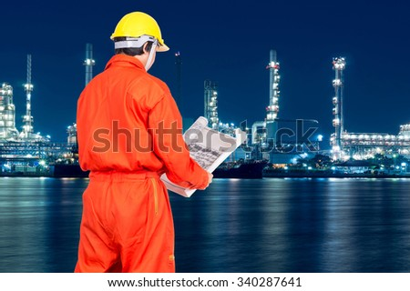 Portrait of Asian engineers looking at the blueprint on Oil and gas refinery or Petrochemical factory at twilight time, industrial concept - stock photo