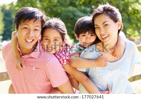 Portrait Of Asian Family Enjoying Walk In Summer Countryside - stock photo