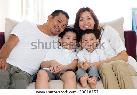 Portrait of asian family sitting on sofa - stock photo