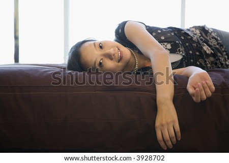 Portrait of Asian female lying on bed looking at viewer.