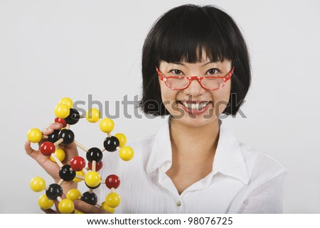 Portrait of Asian female scientist holding chemical model