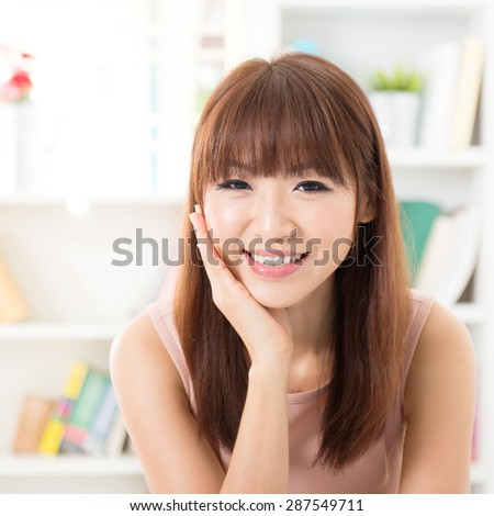 Portrait of Asian girl hand holding face, relaxed and smiling at home, woman living lifestyle indoors. - stock photo