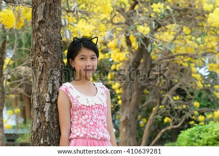 Portrait of asian girl in yellow tabebuia garden at the morning.