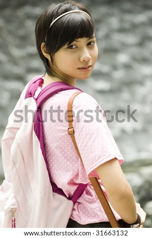 portrait of asian girl looking over her shoulder near a fountain