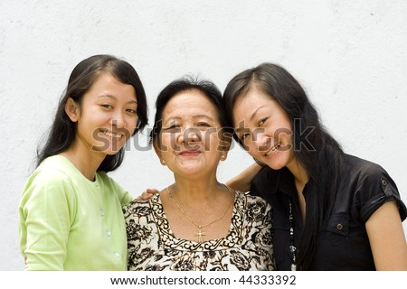 portrait of asian happy family embracing each other, grandmother and two granddaughter - stock photo