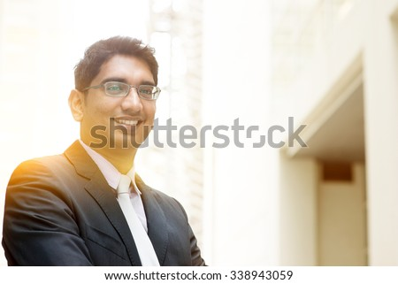Portrait of Asian Indian business man smiling, outside modern office building block, beautiful golden sunlight at background. - stock photo