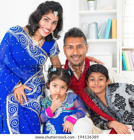 Portrait of Asian Indian family at home, happy parents and children in traditional sari. - stock photo