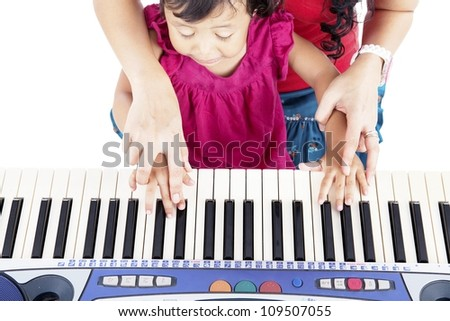 Portrait of asian little girl playing piano with her mother guiding her hands - stock photo