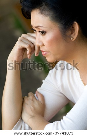 portrait of asian mature woman in sorrow having a serious thought of a problems - stock photo