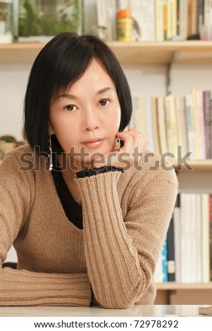 Portrait of Asian mature woman looking at you in home.