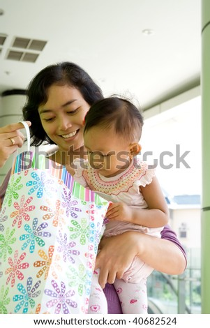 portrait of asian mother and baby girl having fun shopping at the mall - stock photo