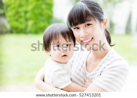 portrait of asian mother and baby relaxing in the garden