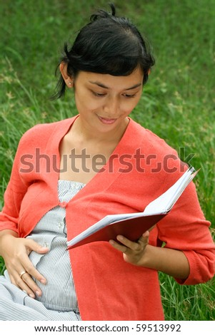 portrait of Asian pregnant woman happy reading pregnancy medical report - stock photo
