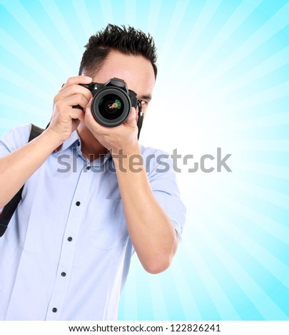 portrait of asian professional photographer ready to take some photo on blue background - stock photo