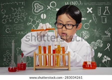 Portrait of asian schoolboy playing chemical in laboratory with doodle on blackboard - stock photo