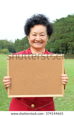 Portrait of Asian senior and daughter holding blank board - stock photo