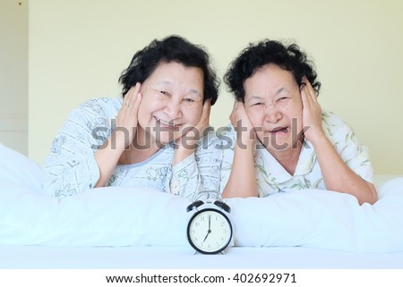 Portrait of Asian senior noisy with alarm clock on bed - stock photo