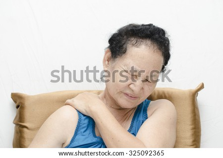 Portrait of asian senior woman shoulder pain expression - stock photo