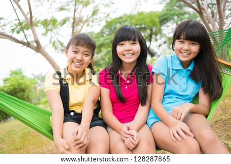 Portrait of asian sisters sitting in the hammock and laughing - stock photo
