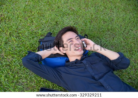 Portrait of asian student use lying on a grass at a campus - stock photo