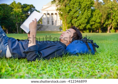 Portrait of asian student with book lying on a grass at a campus - stock photo