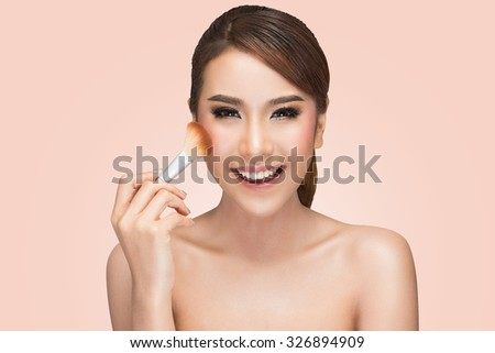 portrait of asian woman applying dry cosmetic tonal foundation on the face using makeup brush, on pink background with clipping path. - stock photo