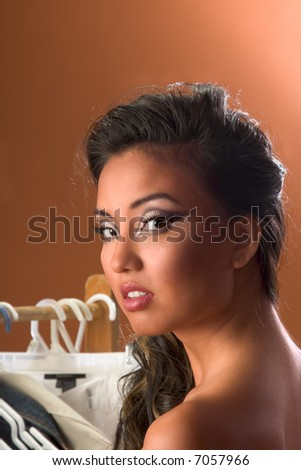 Portrait of Asian woman by clothes rack