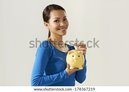 portrait of asian woman holding piggybank and 1 euro coin. Copy space - stock photo