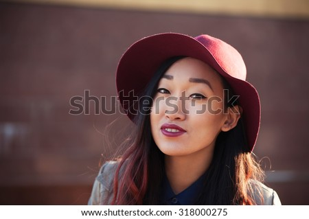 Portrait of asian woman in hat outdoors - stock photo