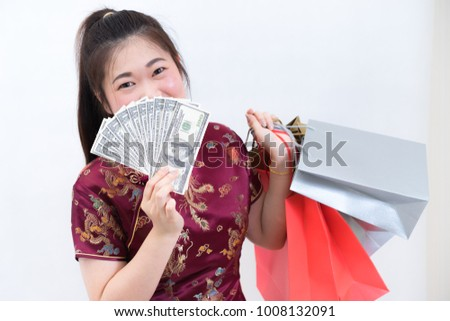 Portrait of asian woman in traditional chinese long dress, cheongsam, black hair, carrying paper shopping bags and dollar banknote as a customer for Chinese New Year festival, celebration time