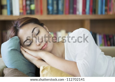 Portrait of asian woman napping on couch with background of book collection on bookshelf - stock photo