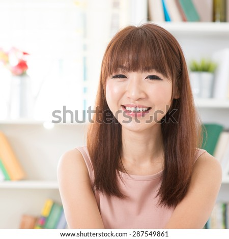 Portrait of Asian woman relaxed and laughing at home, female living lifestyle indoors.