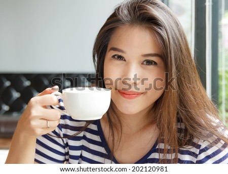 Portrait of asian woman smiling and holding  cup of coffee  - stock photo