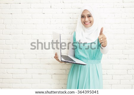 portrait of asian woman wearing hijab holding laptop and giving thumbs up with copy space on white background - stock photo
